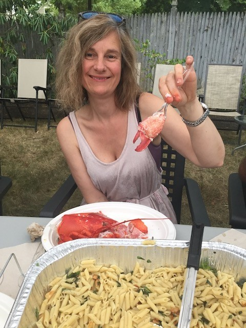 Kat Klingenberg, co-founder of PHIUS, eating lobster in the backyard at Summer Camp
