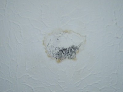 Water spot on a ceiling from condensation on the duct above