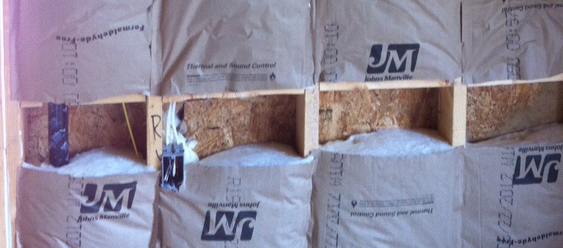 Grade III installation of fiberglass batt insulation with a kraft paper facing, closeup